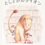 絵本「としょかんライオン」の表紙。図書館でライオンにもたれかかりながら絵本を読む子供たちとそれを見ながら微笑むライオン。