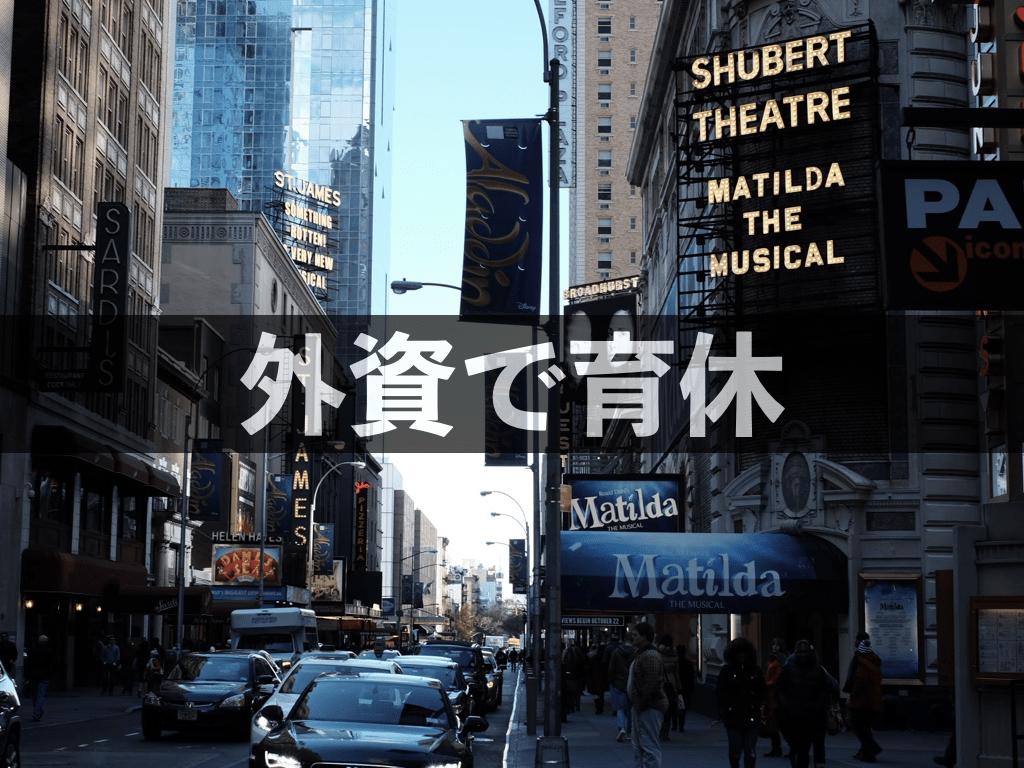 ニューヨーク、ブロードウェイの写真を背景に「外資で育休」の文字