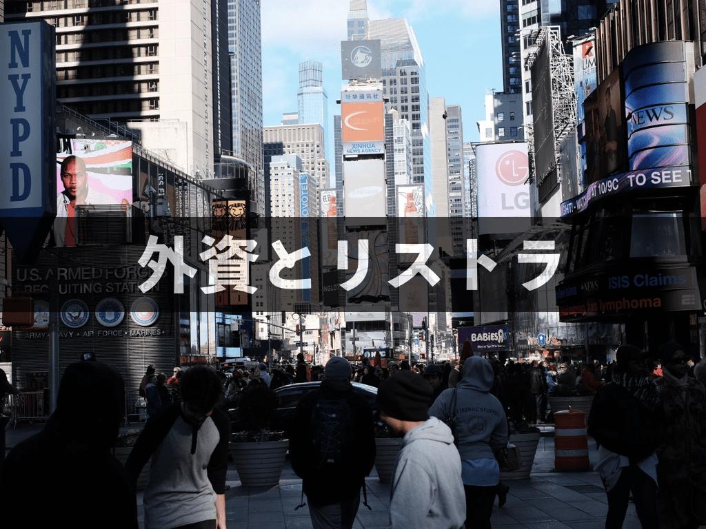 ニューヨーク、タイムズスクエアの写真を背景に「外資とリストラ」の文字